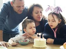 Kid celebrating birthday with his family stock photography