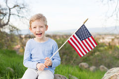 Kid celebrating 4th of july. Smiling boy holding american flag and celebrating 4th of july Royalty Free Stock Photography