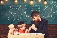 Kid cheerful boxing, beating dad. Playful child concept. Father with beard, teacher teaches son, little boy, while child. Beating him. Teacher and pupil in stock photos