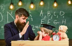 Kid cheerful distracting while studying, attention deficit. Teacher and pupil in mortarboard, chalkboard on background. Playful child concept. Father with stock photography