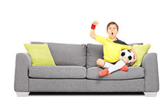 Kid cheering and holding football seated on sofa Stock Photography