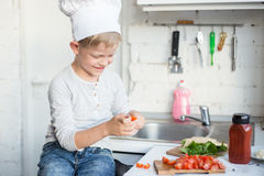 Kid chef is cooking in the kitchen at home. Healthy food Stock Photo