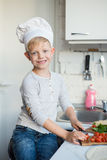 Kid chef is cooking in the kitchen at home. Healthy food Stock Image