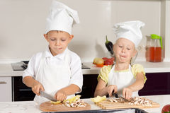 Kid Chefs Busy Slicing Ingredients at Kitchen. Cute Kid Chefs Busy Slicing Ingredients for Pizza at Kitchen Stock Images