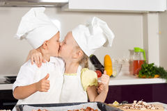 Kid Chefs Kissing at Kitchen Royalty Free Stock Image