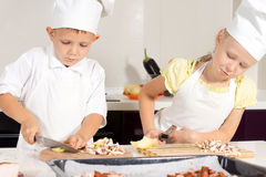 Kid Chefs Slicing Ingredients on Chopping Board Royalty Free Stock Images