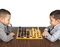 Kid and chess. Six year old and eight year old boys playing chess, isolated on white background Royalty Free Stock Image