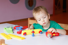 Kid child boy playing with toys Stock Images