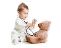 Kid or child playing doctor with stethoscope. And teddy bear isolated on white Stock Photography