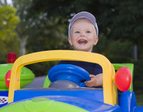 Kid in children's car Stock Photography