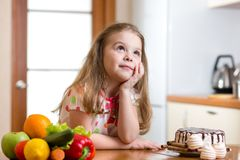 Kid choosing between healthy vegetables and tasty Royalty Free Stock Photography