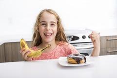 Kid choosing between healthy vegetables and tasty sweets Stock Photo