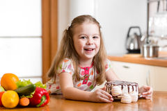 Kid choosing between healthy vegetables and tasty sweets Royalty Free Stock Images