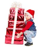 Kid with Christmas gift box. Child in Santa hat with stack gift box. Isolated Royalty Free Stock Photo
