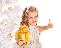 Kid with Christmas gift box. Child with gift box near white Christmas tree. Isolated Royalty Free Stock Photography
