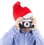 Kid with christmas hat shooting with a retro style camera Stock Image