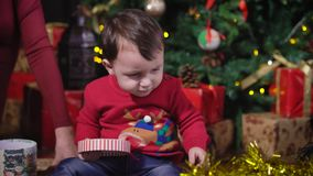 The kid at the Christmas tree. Interested baby playing with a gift box. The kid saw a golden tinsel and pushed her foot stock video