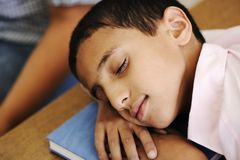 Kid in classroom on desk falling asleep. On his notebook Stock Photography