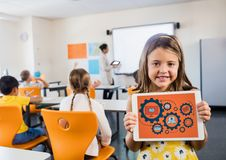 Kid in classroom with tablet showing gear graphics against orange background