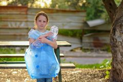 Kid cleaning in park.Volunteer child with a garbage bag cleaning up litter, putting plastic bottle in recycling bag. royalty free stock images