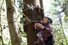 Kid climbing in adventure park Stock Photography