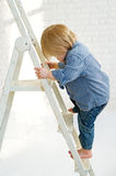 Kid climbing the ladder Stock Images
