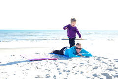 Kid climbing on mother. Child standing on her mother at the beach Royalty Free Stock Photography