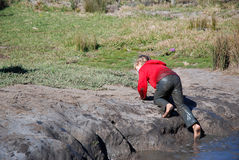 Kid climbing muddy pool Stock Photos