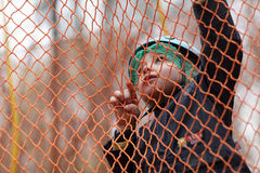 Kid climbing into a net Stock Image