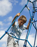 Kid Climbing Ropes. Kid climbing on blue ropes with blue sky background Royalty Free Stock Photo