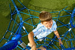 Kid Climbing Ropes. Photographed from above a boy climbing blue ropes Royalty Free Stock Photo