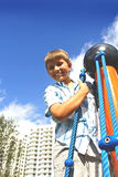 Kid Climbing Ropes. Kid holding on to blue ropes and smiling Royalty Free Stock Photos