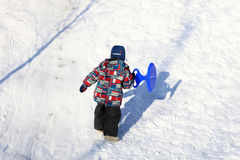 Kid climbing on a snowy hill Royalty Free Stock Images
