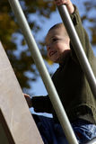 Kid Climbing Up the Slider. With a Smile on His Face Stock Images