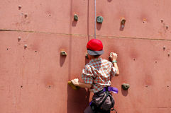 Kid climbing wall Stock Images