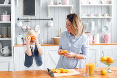 The kid closes his eyes orange. Fooling around. son and young mother in the kitchen eating Breakfast. Royalty Free Stock Images