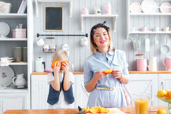 The kid closes his eyes orange. Fooling around. son and young mother in the kitchen eating Breakfast. Stock Photography