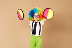 Kid in clown wig and eyeglasses playing catch ball game Royalty Free Stock Photography