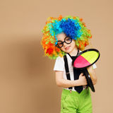 Kid in clown wig and eyeglasses playing catch ball game Stock Images