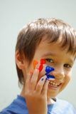 Kid with color on his fingers and face Stock Photo