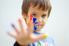 Kid with color on his fingers and face. Kid with color on his fingers and his face looking Royalty Free Stock Photos