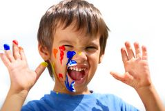 Kid with color on his fingers and face  yelling. Kid with color on his fingers and his face looking Royalty Free Stock Image