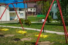 Kid color swing. In the summer park between the houses Royalty Free Stock Images