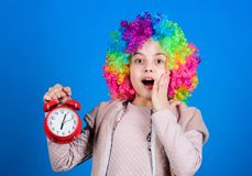 Kid colorful curly wig clown style hold alarm clock. I am not joking about discipline. False alarm. Girl worry about royalty free stock photography