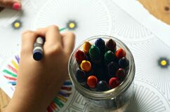 Kid coloring with crayons Stock Photo