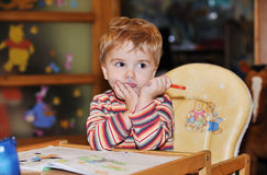 Kid coloring paints thoughtfully Stock Photo