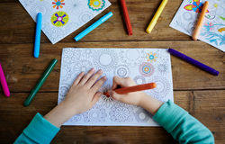 Kid coloring pics. Hands of boy coloring pics with crayons Royalty Free Stock Photography