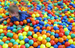 Kid in colourful fun balls. A boy plying in colorful plastic balls in red, yellow, green and blue in a funpark stock photography
