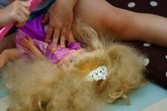 Kid combing hair of princess doll royalty free stock image