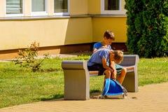 Kid comforting consoling upset sad boy in school yard.  royalty free stock image